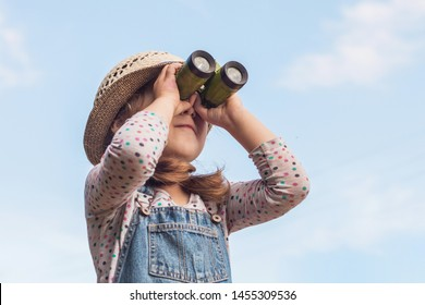Little child looks in binoculars outdoors in sunny summer day against sky background. Happy kid looking up. Young girl in denim overalls and a straw hat. Rustic style.