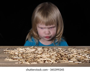 Little child and Lucifer match. Lucifer match are not toys for children. A lot of matches on the table. Child scared. Black background. Dangerous Games with fire