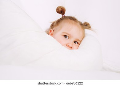 Little child lying on bed at home. 2 years old baby rests under the white blanket.