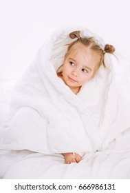Little child lying on bed at home. 2 years old baby rests under white blanket.
