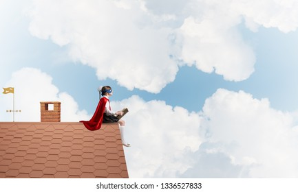 Little child in mask and cape sitting on house brick roof and reading. Mixed media