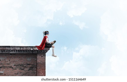 Little child in mask and cape sitting on building roof and reading. Mixed media