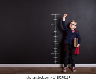 Little child measuring growth near blackboard wall. Cute kid in glasses with book ready for education. Success, motivation concept. Back to school. Little businessman,