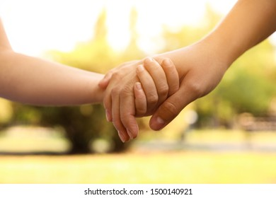 Little child and mother holding hands outdoors, closeup. Family weekend