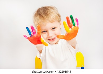 Little child painting. Baby boy with hands in paint. Child painted with fingers. Portrait of adorable blond boy isolated on white background. Close up of smiling face and hands of small boy.