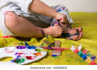 Little child painting feet using colorful paints.