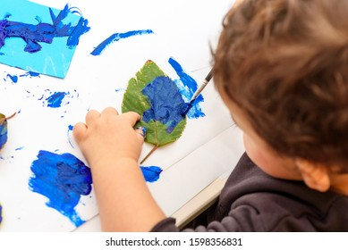 Little child painting leaves blue color, crafts and art therapy. Classic Leaf painting art. Child of stock contributor painting green leaves trendy blue color 2020.