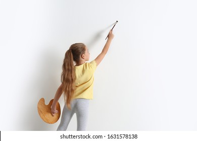 Little child painting on blank white wall indoors, space for text