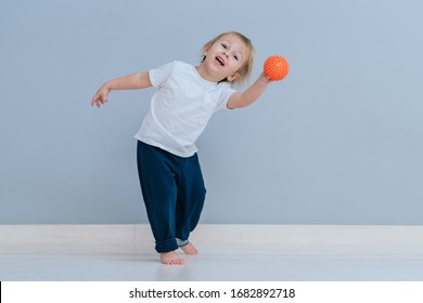 Little child play with orange soft ball over grey wall background in home,full height, exercise and healthy, indulge, concept. Beautiful toddler boy playing with colored small ball kindergarten
