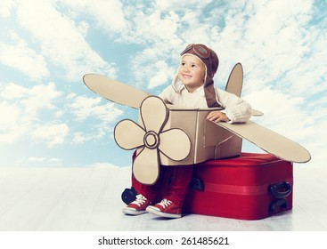 Little Child Playing Airplane Pilot, Kid Traveler Flying in Aviator Helmet on Travel Suitcase, Vacation Trip Concept over Blue Sky Clouds