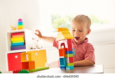 Little child playing with blocks. Boy sitting on the chair at table and building a house