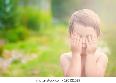 little child is playing hide-and-seek hiding face in sunlight with boke