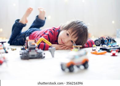 Little child playing with lots of colorful plastic toys indoor, building different cars and objects