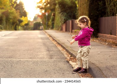Little child playing on street.