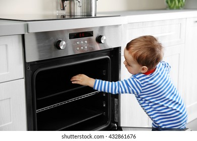 Little child playing with oven in the kitchen