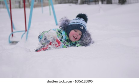 A little child playing with snow in winter Park. Lying and smiling baby on white fluffy snow. Fun and games in the fresh air.