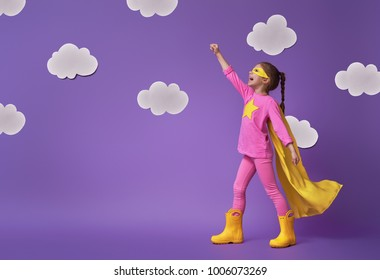 Little child is playing superhero. Kid on the background of bright ultra violet wall. Girl power concept. Yellow, pink and  purple colors.