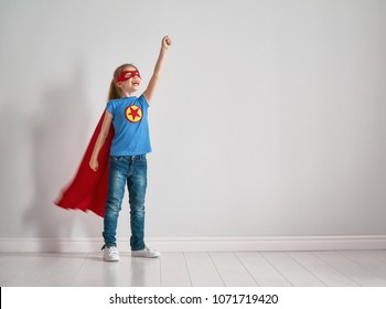Little child is playing superhero. Kid on the background of bright wall. Girl power concept.