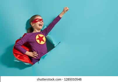 Little child is playing superhero. Kid on the background of bright blue wall. Girl power concept.