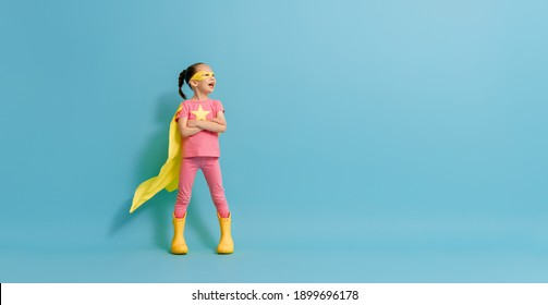 Little child playing superhero. Kid on the background of bright blue wall.