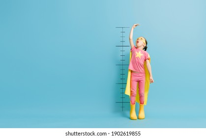 Little child is playing superhero. Kid is measuring the growth on the background of color wall. Girl power concept.