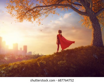 Little child is playing superhero. Kid on the background of autumn landscape. Girl power concept.