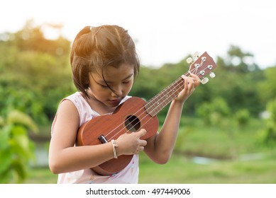 A little child playing ukulele in the garden.