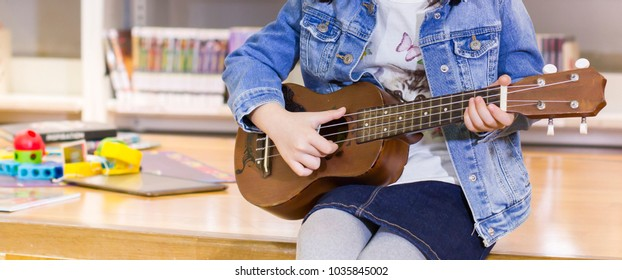 Little child playing ukulele in the library bossanova music in summer time, Cute girl play guitar vintage style, hand picking Guitar ,Ukulele on  the library .