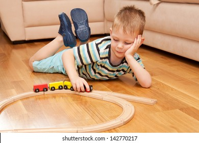 Little child playing with wooden railway on the floor.