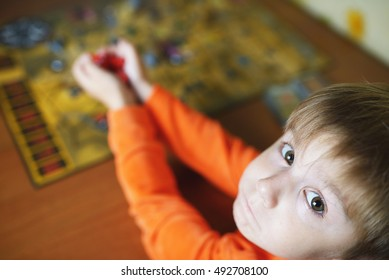 Little child plays board game