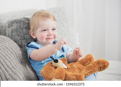 little child plays doctor with teddy bear at home
