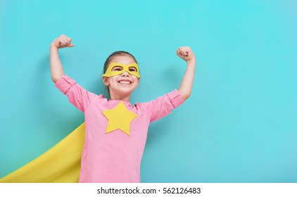 Little child plays superhero. Kid on the background of bright blue wall. Girl power concept. Yellow, pink and  turquoise colors.