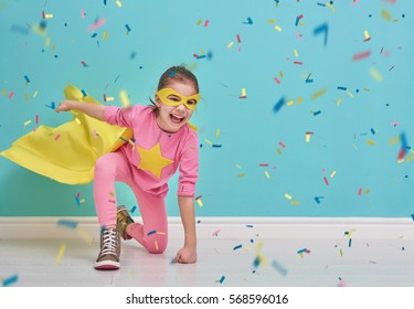 Little child plays superhero. Kid on the background of bright blue wall. Girl is throwing confetti. Yellow, pink and  turquoise colors.