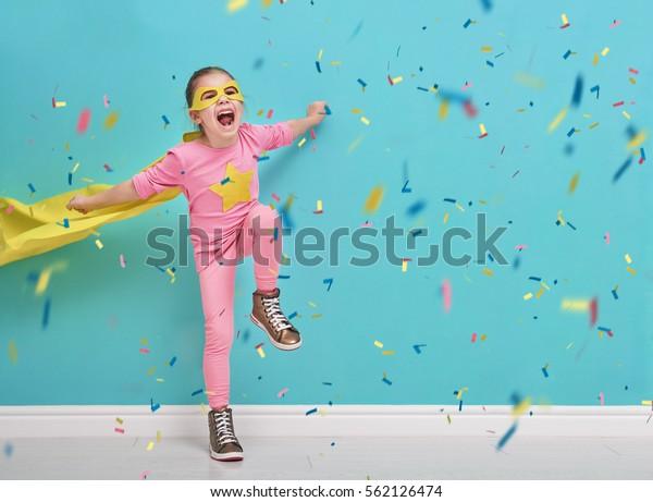 小さな子どもがスーパーヒーローを演じる。明るい青の壁の背景に子ども。女の子は紙吹雪を投げて飛び上がっている。黄色、ピンク、青緑。