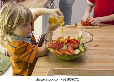 Little child pouring olive oil into mixed salad. Boy cutting tomato while mother cooking in the kitchen.