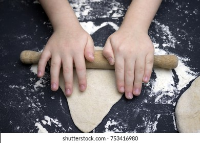 Little child preparing dough for backing. Kid's hands, some flour, wheat dough and rolling-pin on the black table. Children hands making the rye dough for backing bread. Small hands kneading dough
