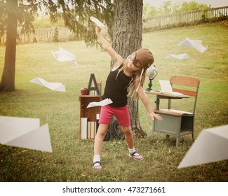 A little child is pretending to be a pilot flying paper airplanes in a classroom outside for a education or creativity concept.