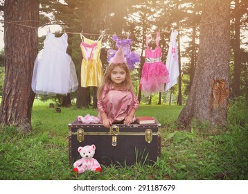 A little child is pretending to be a princess outside with dress up clothes hanging on a clothesline for a imagination or creativity concept.