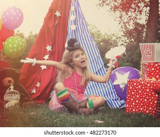 A little child is pretending to perform at a circus theme background with party balloons for an imagination, art or birthday concept.