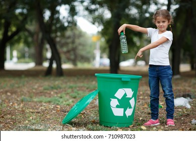 A little child putting the garbage in a green recycling bin on a blurred natural background. Ecology pollution concept.