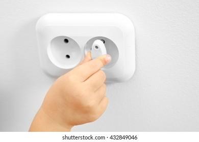 Little child putting plug in power socket