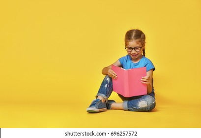 Little child is reading a book. Kid on the background of bright color wall. Education and success concept. Yellow, red and  blue.