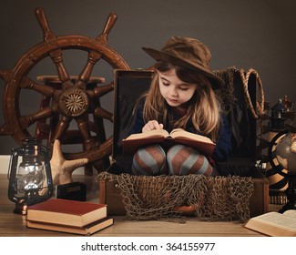 A little child is reading an old book sitting in a travel suitcase with sea props for an imagination or education concept.