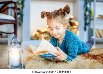 A little child reads a book in the room. Concept New Year, Merry Christmas, holiday, vacation, winter, childhood.