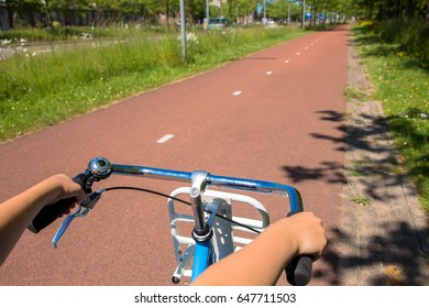 Little child riding a bicycle on bike path. Children's hands hold the handlebar close-up. Eco-friendly transport and healthy lifestyle concept.