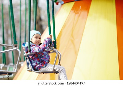 Little child riding on a chaing swing