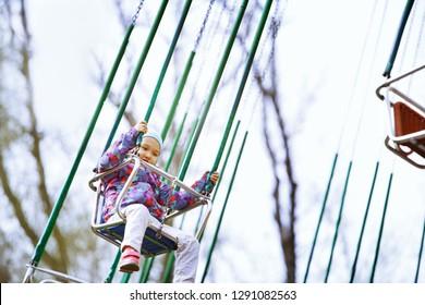 Little child riding on a children chain swing. Amusement park for children lifestyle