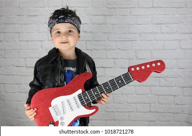 little child with a rock star costume playing a guitar