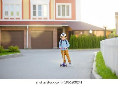 Little child in safety helmet riding scooter to school. Preschooler boy waving hand saying hi. Safety kids by way to school. Back to school and education for children concept.