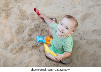 Little child in sandpit. Portrait of happy little baby boy enjoying playing with sand toys on summer day.